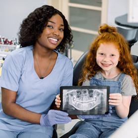 Dental Hygienist teaching a child how to brush teeth.