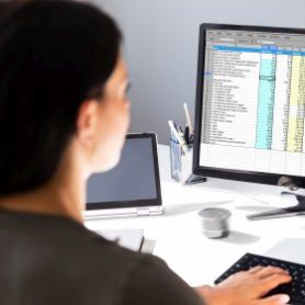 medical billing specialist woman looks at computer screen