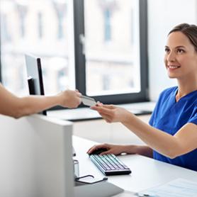 Insurance specialist shows paperwork on clipboard to elderly woman